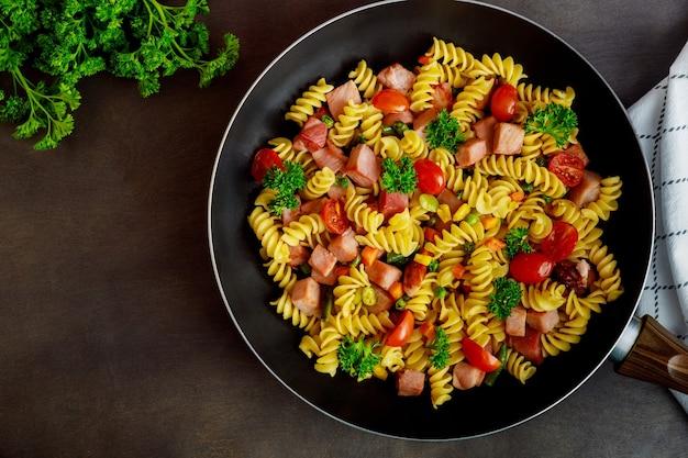 Pâtes rotini aux pois verts, jambon et persil dans la poêle. cuisine italienne.