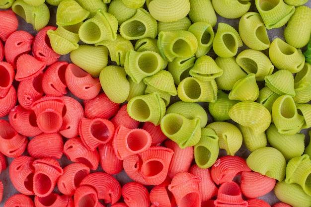 Pâtes rouges et vertes dans des sauces colorées.