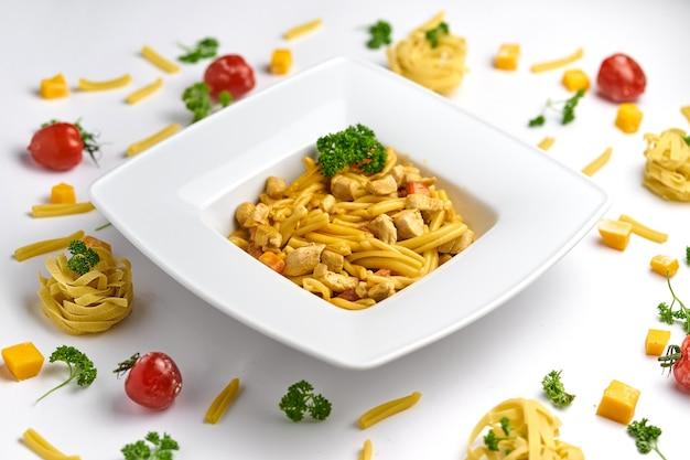 Pâtes à la sauce tomate au poulet, tomates décorées de persil sur une plaque en bois