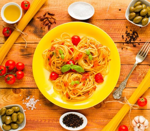 Pâtes à la sauce tomate et autres composants sur une table en bois