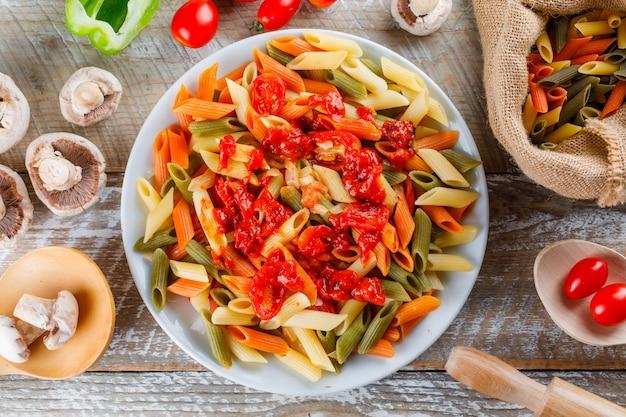 Pâtes avec sauce, tomate, champignon, rouleau à pâtisserie, poivre dans une assiette
