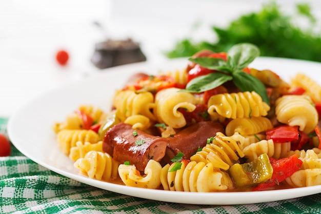Pâtes à la sauce tomate avec saucisse, tomates, basilic vert décorées dans une assiette blanche sur une table en bois.