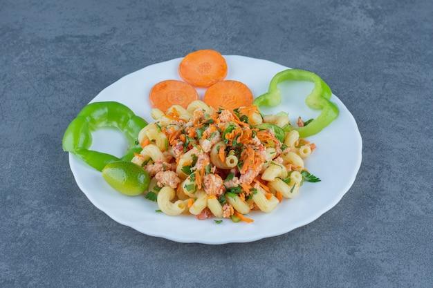 Pâtes savoureuses aux légumes hachés sur plaque blanche.