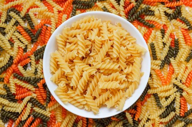Pâtes sèches dans une assiette blanche sur une table de macaroni, mise à plat.