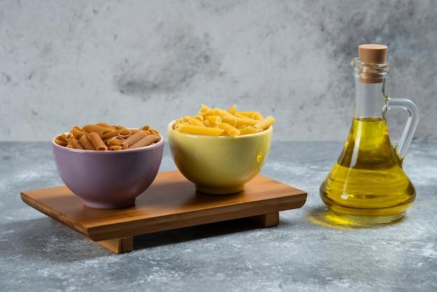 Pâtes de semoule crues jaunes et brunes avec une bouteille en verre d'huile.