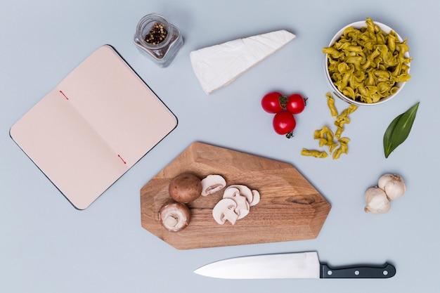 Des pâtes et son ingrédient avec un journal intime vide sur un fond uni