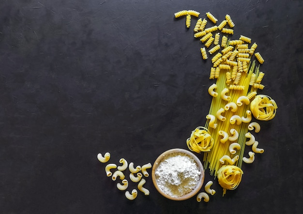 Les pâtes sont disposées en forme de spaghetti de pâtes italiennes crescent, tagliatelles, fusilli, cavatappi sur fond noir.