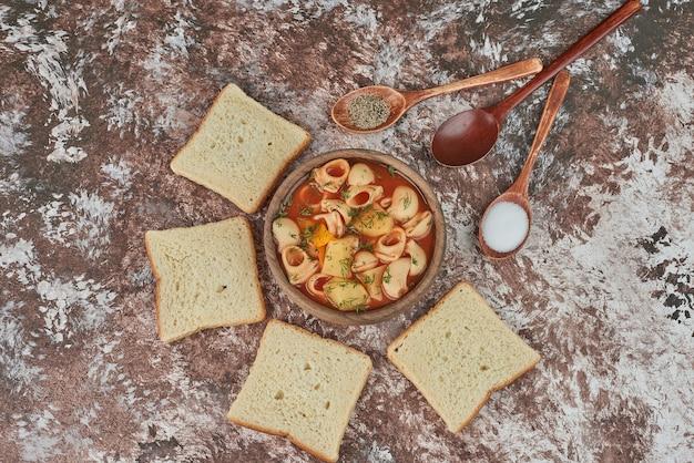 Pâtes à la soupe de tomates avec du pain.