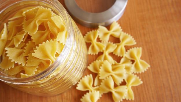 Pâtes sous forme d'arcs dispersés dans un bocal en verre. pâtes italiennes faites à la main sur le fond en bois.