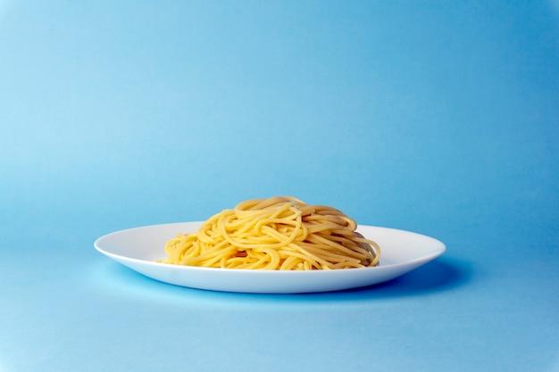 Pâtes spaghetti sur une assiette blanche sur fond bleu