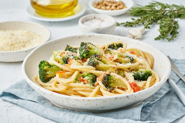 Pâtes spaghetti au brocoli, bucatini aux poivrons, ail, pignons de pin. table blanc clair. vue de côté