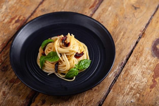 Pâtes spaghetti aux légumes, poivre, feuilles de basilic sur une plaque ronde noire sur fond de bois vintage rustique brun