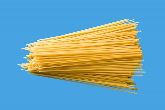 Pâtes spaghetti crues sur fond bleu