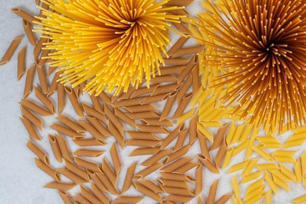 Pâtes spaghetti crues et pâtes penne, sur le marbre.