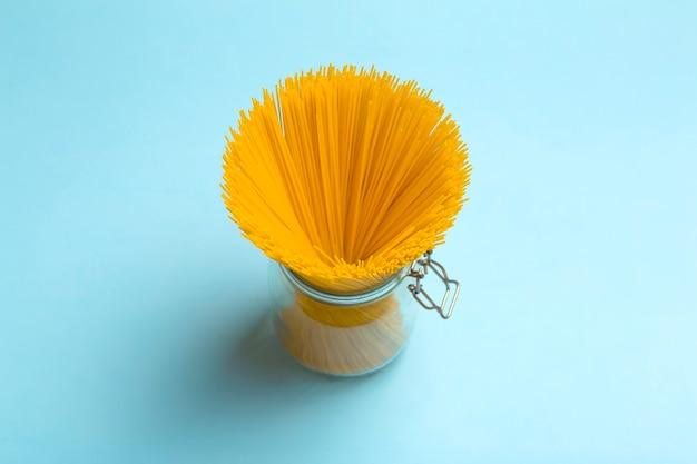 Pâtes spaghetti sur fond bleu blanc. spaghettis isolés frais crus dans un bocal avant de préparer la nourriture italienne.