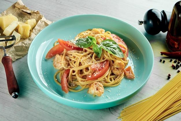 Pâtes spaghetti italiennes avec sauce blanche, crevettes et parmesan servi dans une assiette bleue sur une table en bois. nourriture de restaurant. fruits de mer
