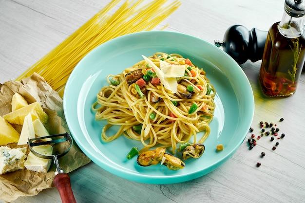 Pâtes spaghetti italiennes avec sauce blanche, moules et parmesan servies dans une assiette bleue sur une table en bois. nourriture de restaurant. fruits de mer