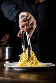 Pâtes spaghetti italiennes en train d'être cuites et plaquées par le chef