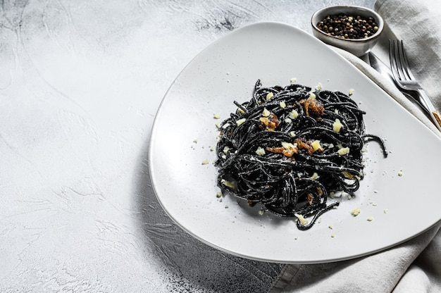Pâtes spaghetti noires au thon en sauce à la crème. fond gris. vue de dessus. copiez l'espace.