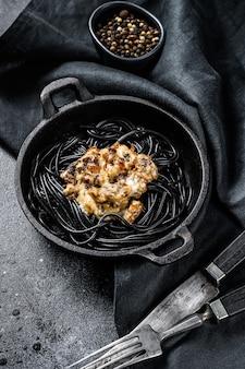 Pâtes spaghetti noires à l'encre de seiche dans une casserole. boeuf à la sauce au poivre. fond noir. vue de dessus.