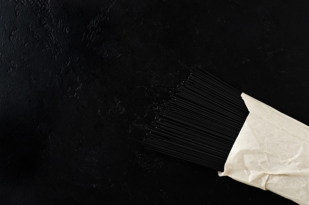 Pâtes spaghetti noires à l'encre de seiche dans un sac en papier sur une surface de béton noir
