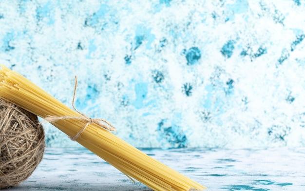 Pâtes spaghetti non cuites et fil sur fond bleu. photo de haute qualité
