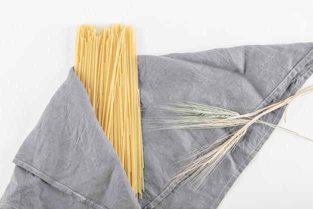 Pâtes spaghetti non cuites sur nappe grise avec du blé. photo de haute qualité