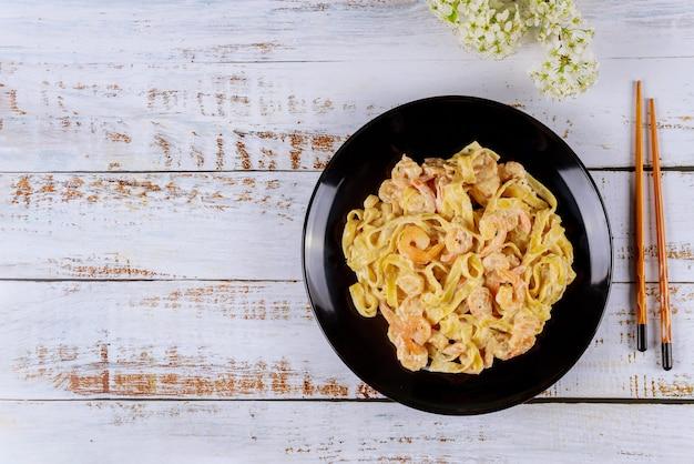 Pâtes spaghetti à la sauce alfredo et crevettes en plaque noire.