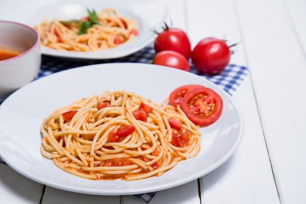 Pâtes à spaghetti avec sauce tomate sur fond de bois