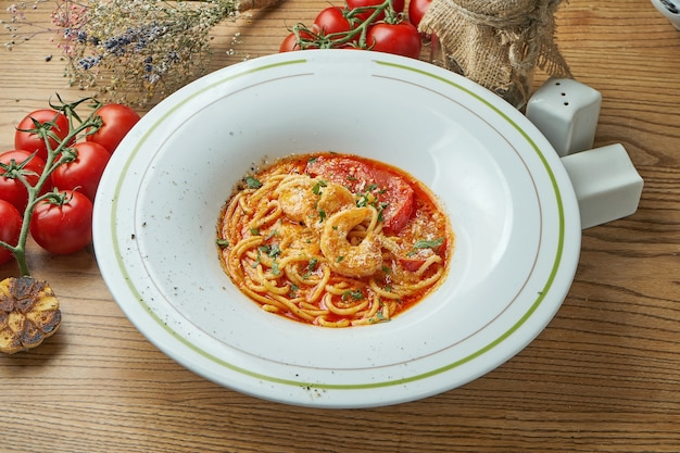 Pâtes spaghetti tom yam aux crevettes, parmesan et sauce rouge, servies dans une assiette blanche sur une table en bois. cuisine italienne