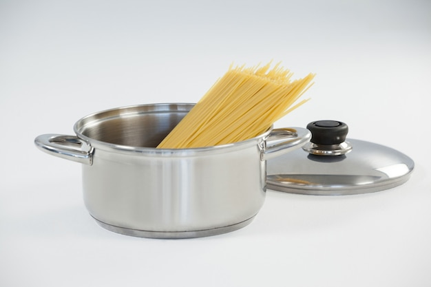 Pâtes spaghetti en ustensile sur fond blanc