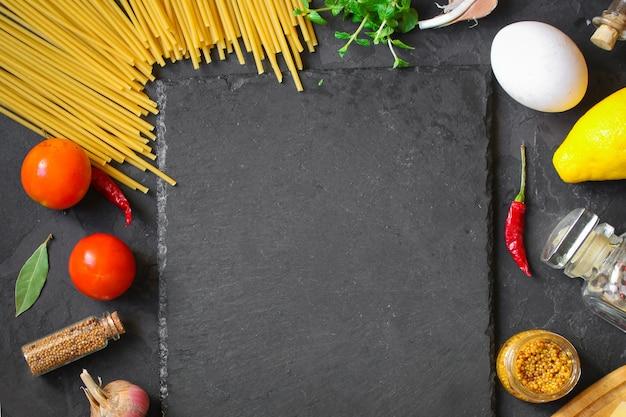 Pâtes, spaghettis ou bucatini et ingrédients de la sauce tomate. fond de nourriture. espace de copie