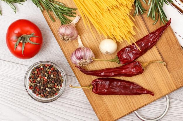 Pâtes ou spaghettis avec des ingrédients pour la cuisson de la viande ou du poisson sur une planche à découper en bois. ail, piment de la jamaïque dans un bol en verre, piment, tomate, oignon et romarin. vue de dessus.