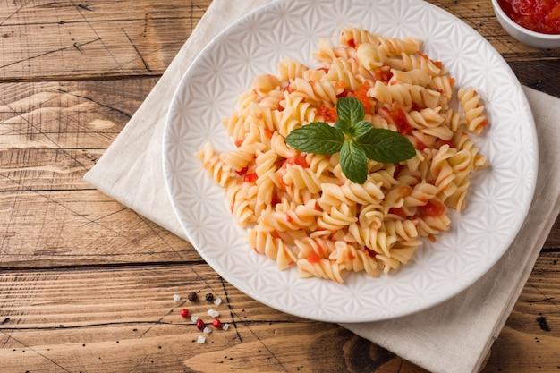 Pâtes en spirale mélangées avec des tomates cerises et de la sauce tomate sur une assiette.