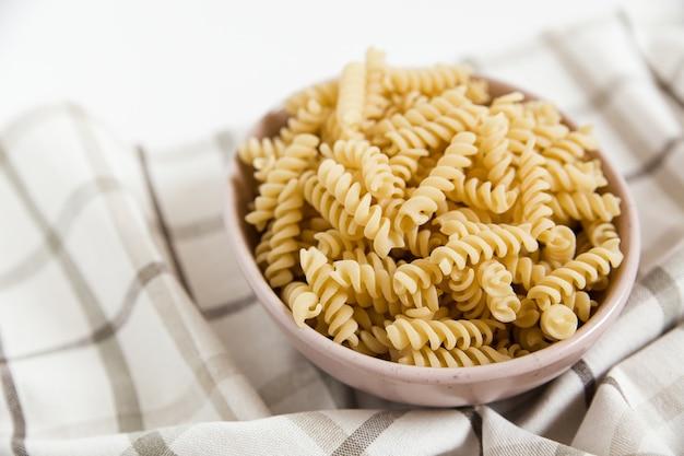 Pâtes en spirale non cuites dans l'assiette en céramique