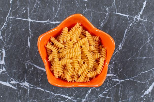 Pâtes en spirale non cuites dans un bol orange.