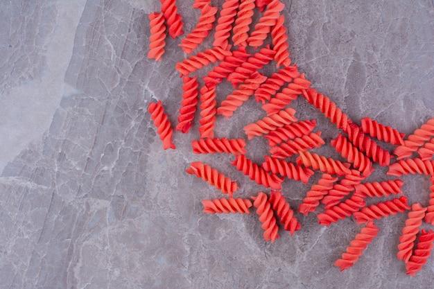 Pâtes en spirale rouge sur espace en marbre.