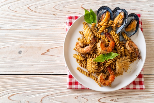 Pâtes en spirale sautées aux fruits de mer et sauce au basilic - style cuisine fusion