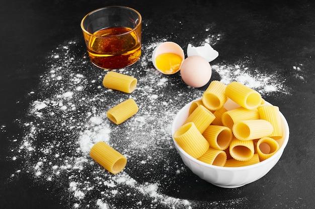 Pâtes sur une surface bleue avec des œufs et du vinaigre.
