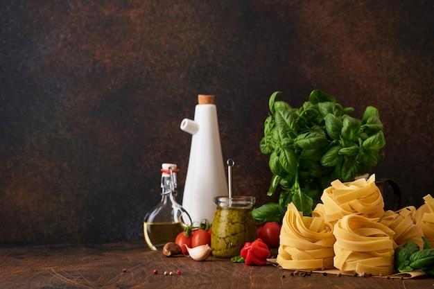 Pâtes tagliatelles maison en papier brun sur fond blanc avec de l'huile d'olive, pesto de sause, basilic et ail