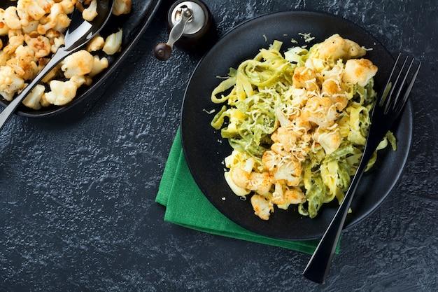 Pâtes tagliatelles en sauce crémeuse au chou-fleur cuit au four dans une assiette sur un fond sombre.