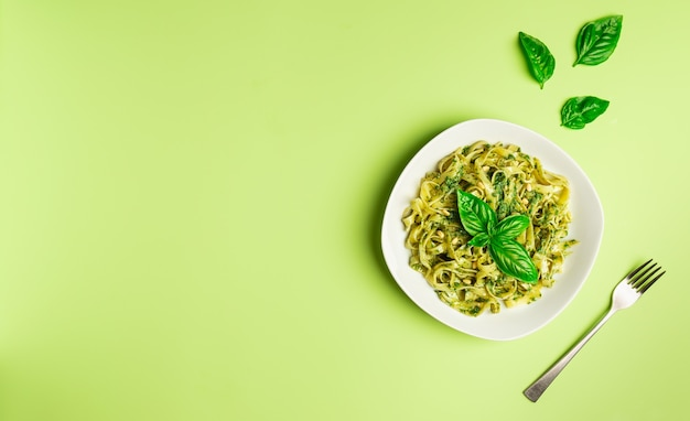 Pâtes tagliatelles sauce pesto basilic et pignons de pin sur fond vert clairdesign minimaliste