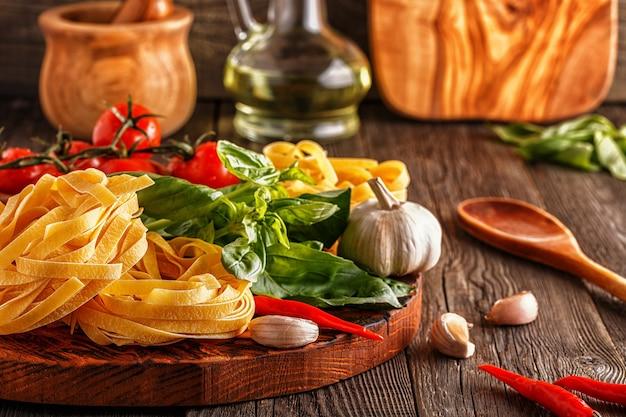 Pâtes, tomates, ail, poivron et basilic sur le vieux bois.