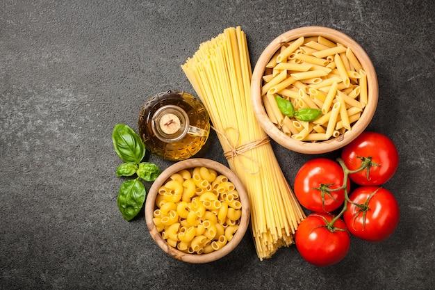 Pâtes, tomates et huile d'olive sur fond noir