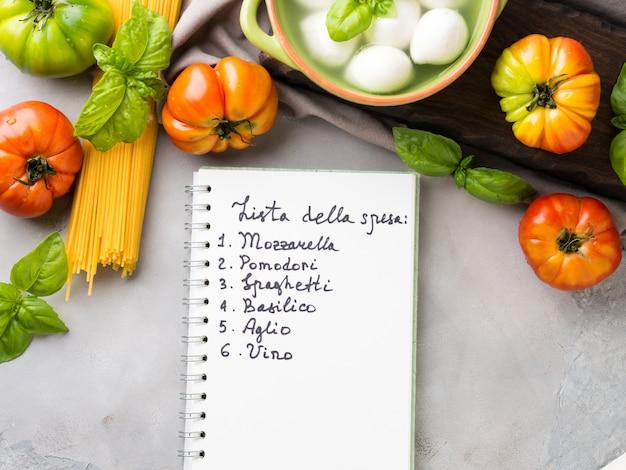 Pâtes, tomates, mozzarella nature morte sur fond gris rustique. liste de produits traditionnels et alimentation pour spaghettis à la tomate en italien