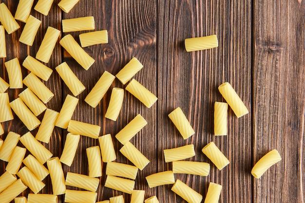 Pâtes tortiglioni dispersées à plat sur une table en bois