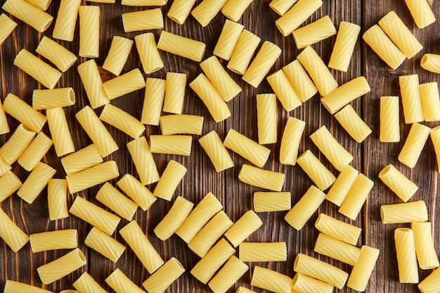 Pâtes tortiglioni épars sur table en bois, mise à plat.