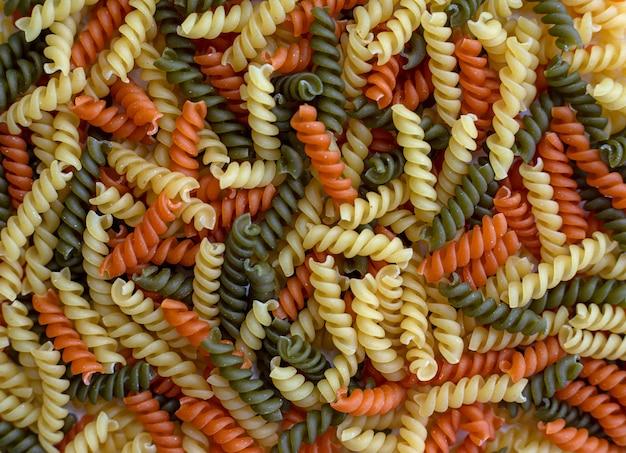 Pâtes tricolores, sèches et crues, nourriture pour le fond
