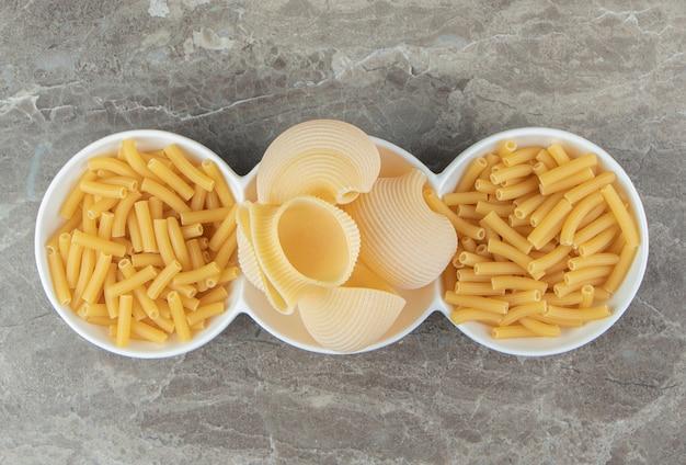 Pâtes en tube et coquillage dans des bols blancs