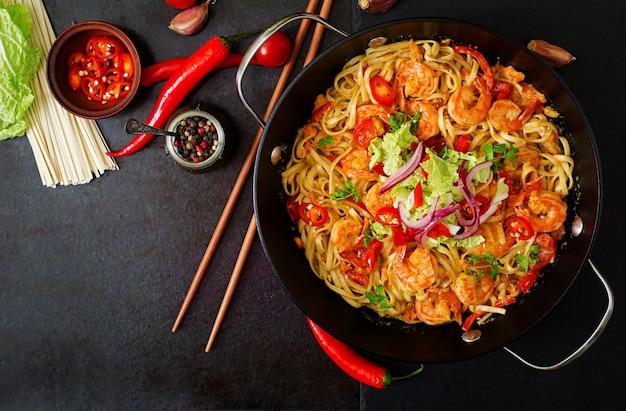 Pâtes udon aux crevettes, tomates et paprika. vue de dessus